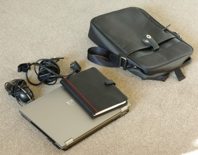 A laptop, charger, mouse and notepad with the bag