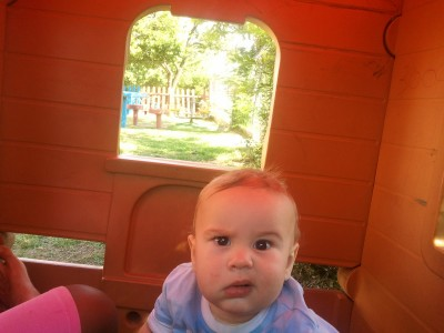 Photo of Joen in a Wendy house, with a quizzical expression